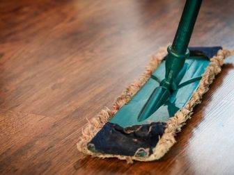 Green Swiffer on a wood floor.