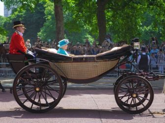 The queen of England riding in a carriage
