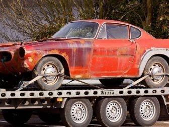 Old red car being towed