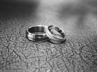 Silver wedding bands on a black surface