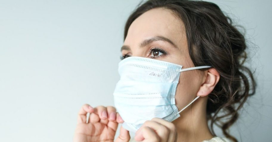 Woman putting on a disposable facemask