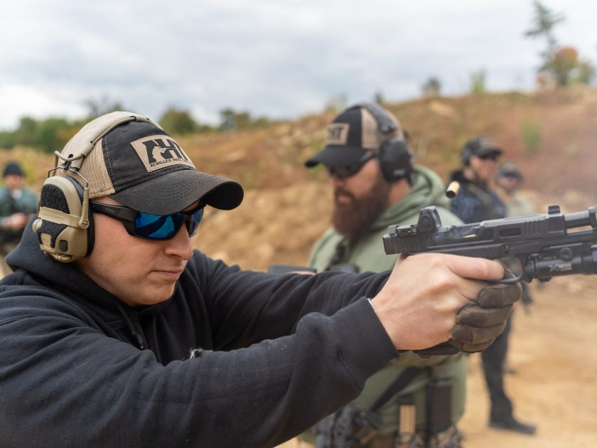 Man in hat and noise cancelling headphones aiming a gun at a shooting range.