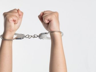 Person holding up hands in hand cuffs