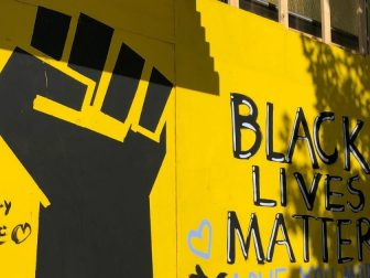 Black Lives Matter mural on a yellow wall