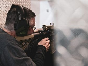 Man with noise canceling headphones on at a gun range.