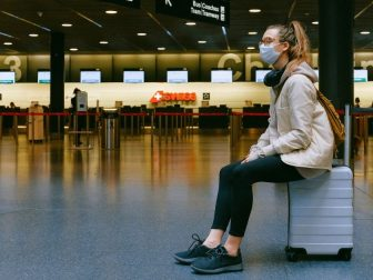 Girl in mask sitting on a suitcase in an airport
