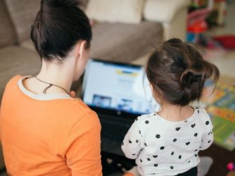 Mom teaches daughter for work on laptop.
