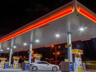 Car filling up on gas at a gas station at night