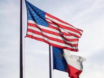 The United States flag flying above the Texas state flag