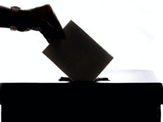Silhouette of a hand putting an envelope into a box
