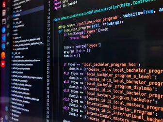 Black computer screen showing coding