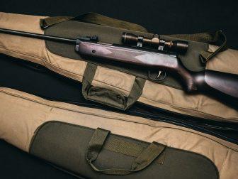 Gun sitting on top of a soft-shell gun case