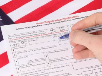 Man filling out Voter Registration Application with USA flag in background