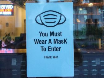 Mask sign in window of storefront.