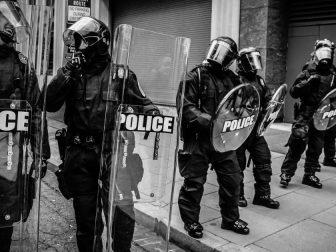 Riot police waiting on a city street sidewalk