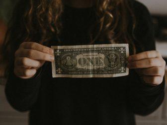 Girl holding a one dollar bill
