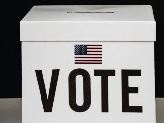 """White box with the word """"vote"""" and an American flag printed on it"""