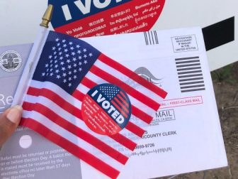 Person holding a mail-in ballot and a miniature American flag
