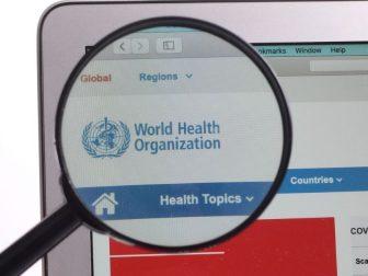 WHO World Health Organization website under magnifying glass