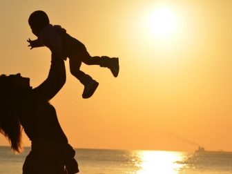 Silhouette of woman and baby on the beach
