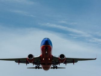 Red and blue airplane against a blue sky