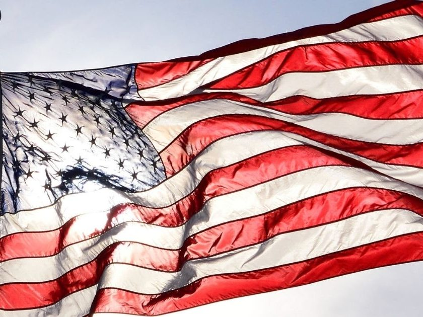 The above stock photo shows an American flag waving in the wind.