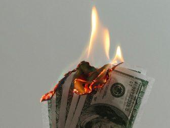 Hand holding dollar bills on fire