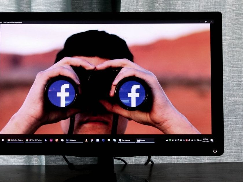 Television showing man looking through binoculars with the Facebook logo in the lens.
