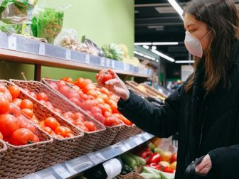 Woman in face mask grocery shopping