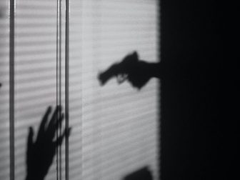 Silhouette of hand holding a gun