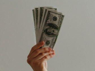Hand holding 100 dollar bills