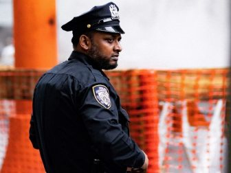 NYC police officer standing in front of orange fencing