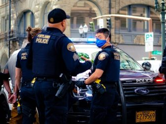 Portland police officers standing around a police car