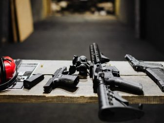 Black rifle on a brown wooden table