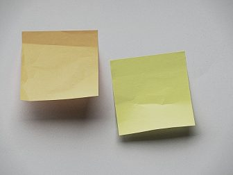 two sticky notes on a blank, white wall