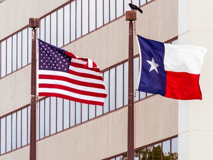 US and TX flags in front of building