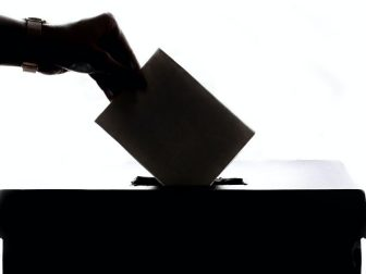 Silhouette of hand placing ballot in box