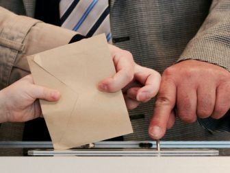 The above stock photo shows someone voting.