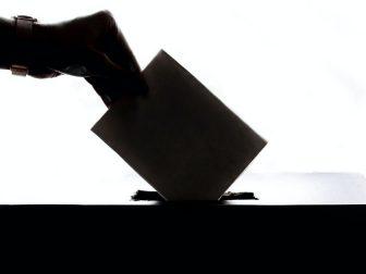 Hand putting ballot into a box
