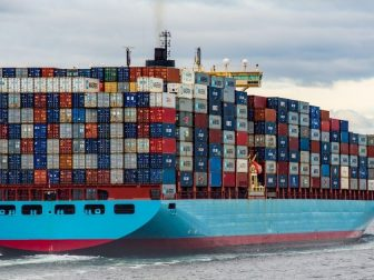 Cargo ship with stacked crates sailing in the water