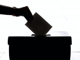 Shadow of hand dropping ballot in box