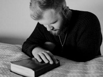 Grayscale Photo of a Bearded Man Praying