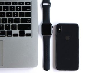 Macbook, Apple Watch, and iPhone lined up on a white surface