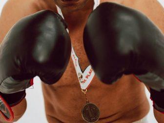 Boxer holding up black gloves