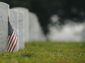 US flag on green grass next to headstone