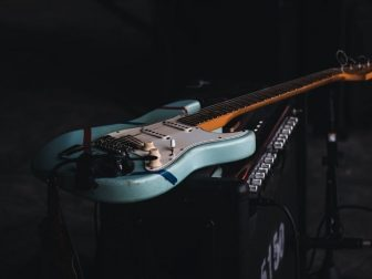 Teal and brown electric guitar sitting on an amp