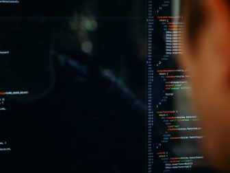 Person facing computer desktop with coding