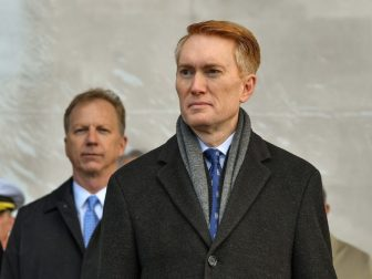 Sen. James Lankford (R-OK) stands for the parading of the colors during the commissioning ceremony of littoral combat ship USS Tulsa (LCS 16).