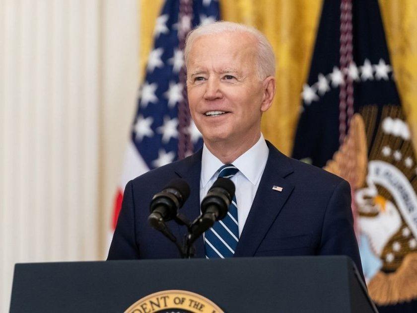 President Joe Biden speaks at the podium.