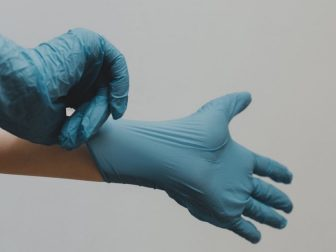 Hands putting on blue latex gloves